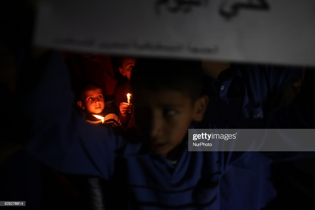 A Palestinian child shouts slogans to resolve Gaza power crisis while he holds a candle during a protest organized by the Democratic Front for the...