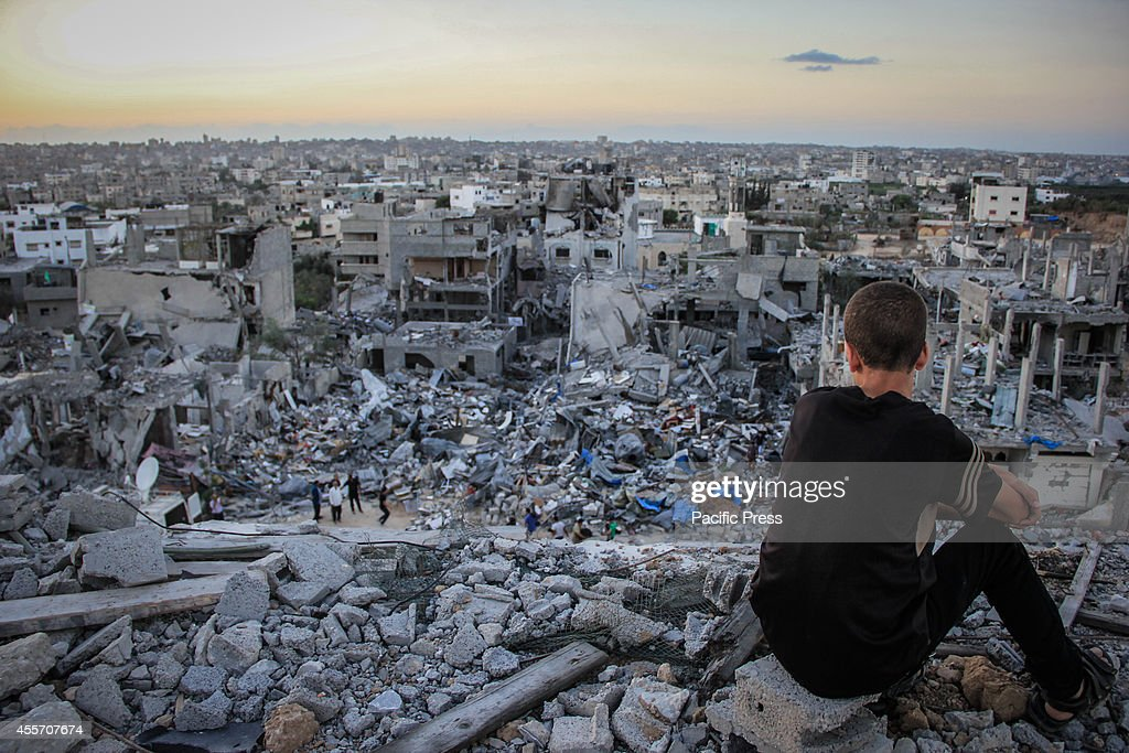 Palestinian child sits above the ruins of his ruined home and looks at thousands of homes destroyed because of the war on Gaza