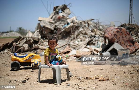 A Palestinian child sits in front of the rubble of buildings which were destroyed during the 50day war between Israel and Hamas militants in the...