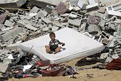 A Palestinian child sits on a mattress on the rubble of a house which was destroyed in an Israeli air strike on Abasan east of the southern Gaza...