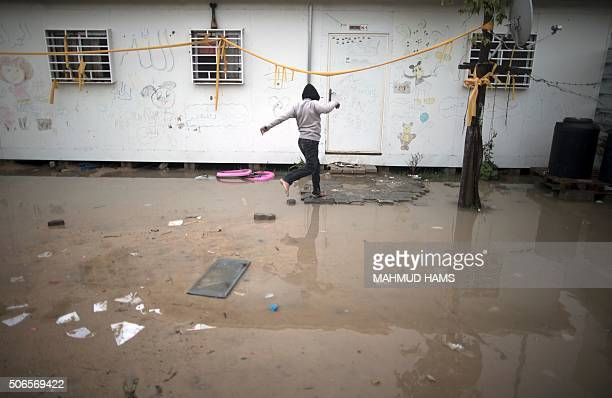 Palestinian child skips barefoot over a puddle outside their temporary housing during a winter storm in Beit Hanoun in the northern Gaza Strip on...