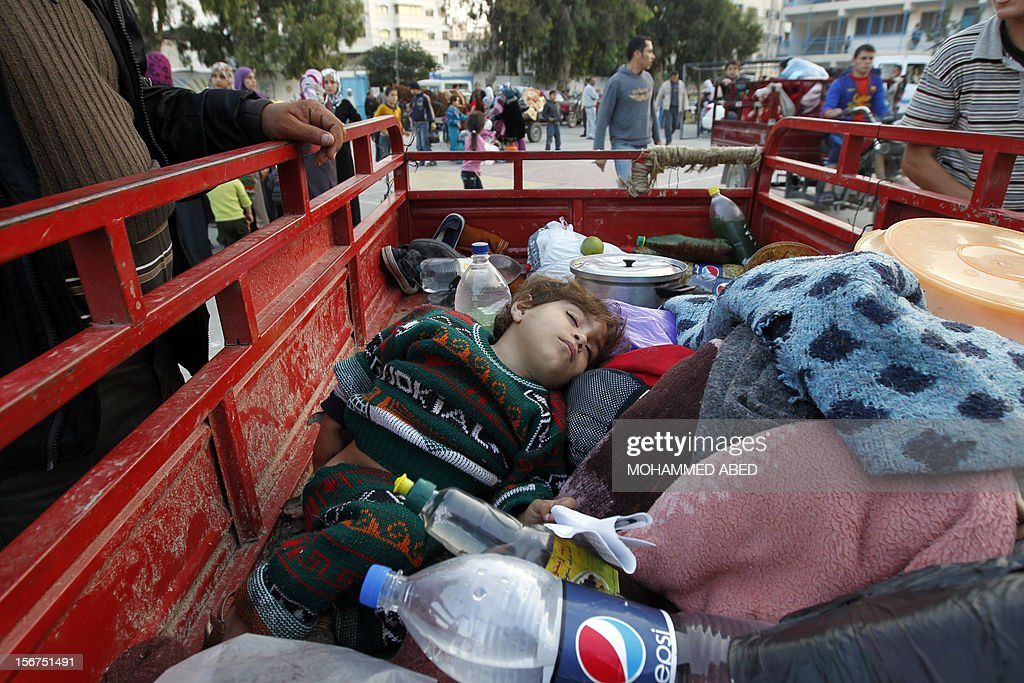 A Palestinian child sleeps on the back of a truck after his family evacuated their homes to take shelter at a United Nations (UN) school in Gaza City on November 20, 2012. A group of 38 aid agencies urged the international community to take action to secure a ceasefire in Gaza to prevent 'another widespread humanitarian disaster.'