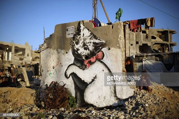 A Palestinian child stands next to a mural of a kitten said to have been painted by British street artist Banksy on the remains of a house that was...
