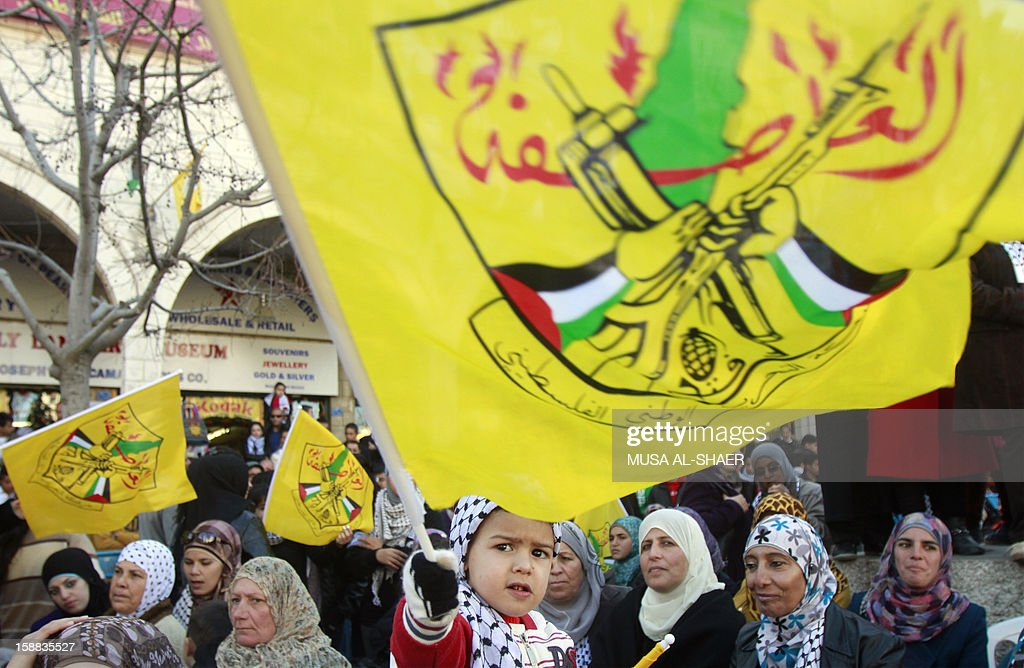 A Palestinian child waves the Fatah movement flag amid supporters of Palestinian leader Mahmud Abbas in front of the Church of the Nativity in the West Bank city of Bethlehem, on December 31, 2012, during celebrations marking the 48th anniversary of the movement's founding. AFP PHOTO/MUSA AL-SHAER