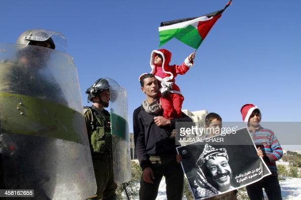 A Palestinian child wearing a Santa Claus costume waves his national flag as another holds a poster bearing the portrait of late Palestinian leader...