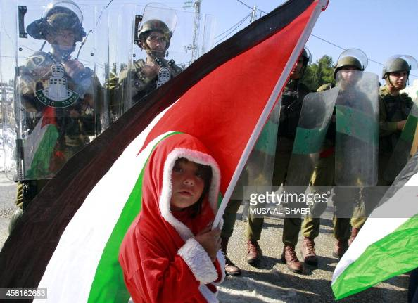 A Palestinian child wearing a Santa Claus costume waves his national flag in front of Israeli troops during a weekly demonstration on December 20...