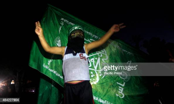 Palestinian child wearing Hamas mask flashing sign of victory as people celebrate after a deal had been reached between Hamas and Israel over a...