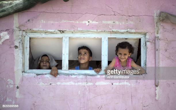 TOPSHOT Palestinian children are seen looking outside a window during a heatwave at alShati refugee camp in Gaza City on July 2 2017 / AFP PHOTO /...