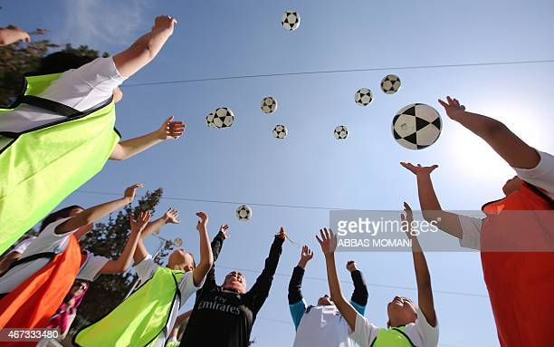 Palestinian children attend a football training session given by Spanish club Real Madrid in the West Bank city of Ramallah on March 23 2015 as part...
