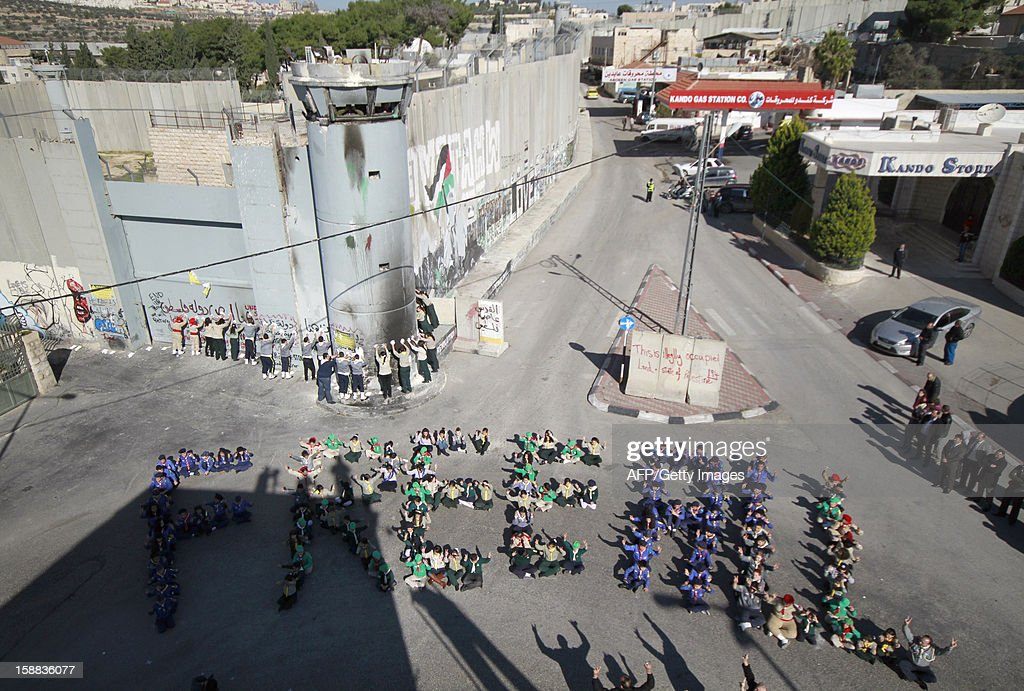 Palestinian children attend an activity by the 'Project Peace on Earth' to send out a message of peace by lining up in a shape of the words 'FREE ALL' designed by international environmental artist John Quigley, near the Israeli built controversial separation barrier at the main entrance of the West Bank town of Bethlehem on December 31, 2012.