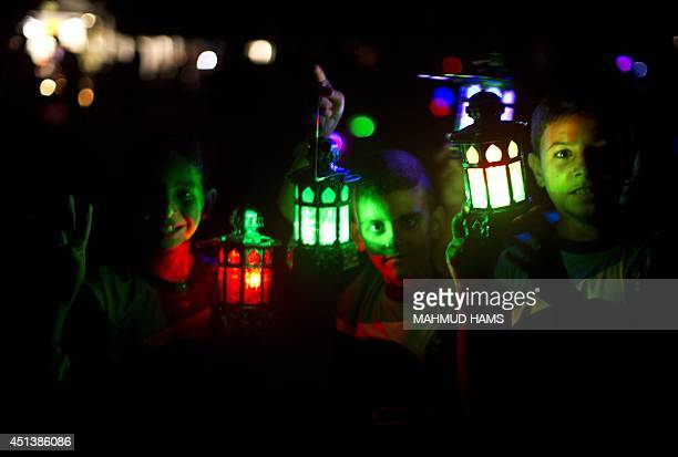 Palestinian children carry traditional Ramadan lanterns in Gaza city on June 28 during a demo against the seige on the Gaza strip a day before the...