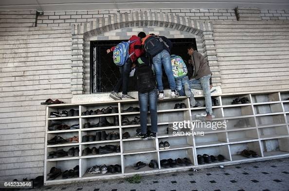 TOPSHOT Palestinian children climb on a window in Rafah in the southern Gaza Strip on February 25 during the funeral of 23yearold Palestinian Obayd...