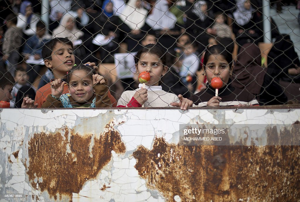 Palestinian children eat sweet apples during a graduation ceremony for a military-style training programme in Gaza City on January 14, 2014. Some 13,000 students joined the course, which is aimed at preparing them for 'liberating Palestine from Israel', Hamas officials said.