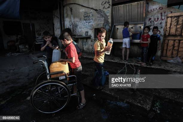 Palestinian children fill jerricans with drinking water from public taps during the Muslim holy month of Ramadan at the Rafah refugee camp in the...