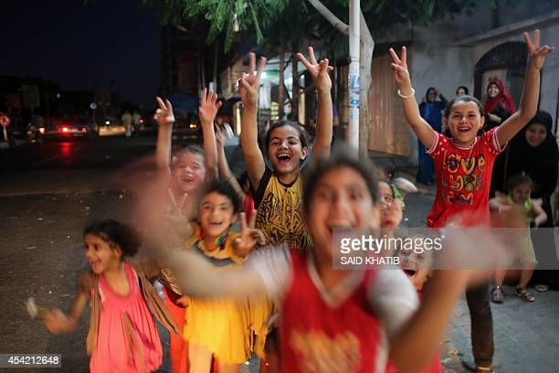 Palestinian children flash the sign of victory as people gather in the streets to celebrate after a deal had been reached between Hamas and Israel...