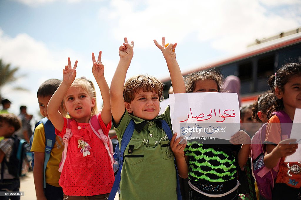 Palestinian children flash victory sign and hold a placard reading 'Remove the embargo' during a demonstration at the Rafah border crossing between the Gaza Strip and Egypt on September 29, 2013 in Rafah town, southern Gaza strip. Hundreds of Palestinian children staged a demonstration on Sunday outside Rafah crossing with Egypt in protest of the long-time closure of the terminal by Egyptian authorities.
