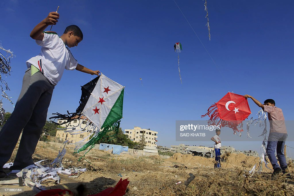 Palestinian children fly kites bearing the Palestinian (top), Turkish (R) and Syria's former independence flag which has been adopted by the rebels forces fighting agianst Syrian pro-government forces in Syria (L) to show their solidarity with the countries during an event organised by Hamas in Rafah town, in the southern Gaza Strip on June 29, 2013.