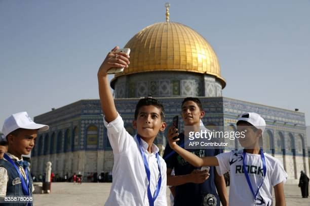 Palestinian children from the Gaza Strip pose for a picture near the Dome of the Rock mosque in the AlAqsa mosque compound in Jerusalem's old city on...