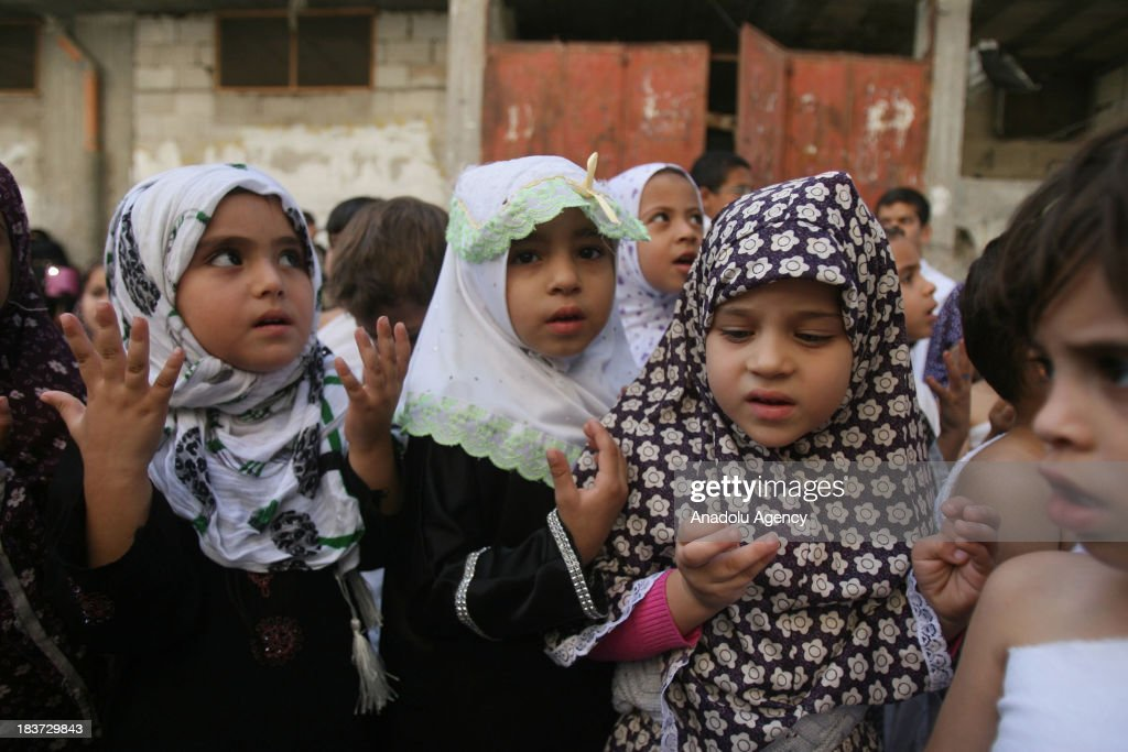 Palestinian children gather around a makeshift cube representing the holy Kaaba on October 09, 2013 in Rafah, southern Gaza Strip, as part of training children how to perform Hajj pilgrimage. Muslims from around the world flood Saudi city of Mecca to perform the annual Hajj pilgrimage, which is one of the five pillars of Islam.