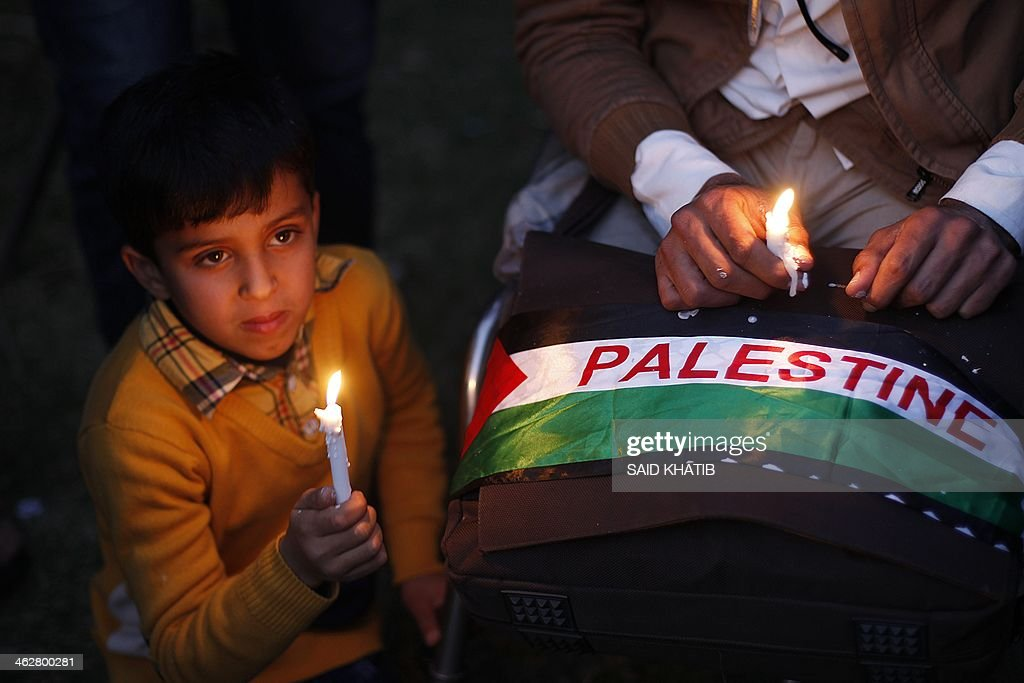 Palestinian children hold candles as they take part in a rally to show solidarity with Palestinian refugees in Syria's main refugee camp of Yarmuk, on January 15, 2014 at Deir al-Balah refugee camp in the central Gaza Strip. Gaza's Islamist rulers Hamas urged militants to leave the Yarmuk Palestinian refugee camp in southern Damascus in order to save residents from ongoing bloodshed. Hamas called for an 'aid channel to be opened up immediately' to the camp, saying Palestinian refugees were not a 'party to the conflict' and should be spared the violence of Syria's nearly three-year civil war.