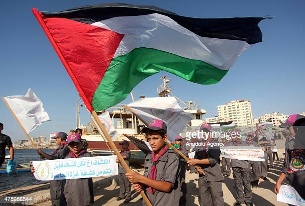 Palestinian children hold national flags as they gather at Gaza Port to protest Israeli blockade the Third Gaza Freedom Flotilla in international...