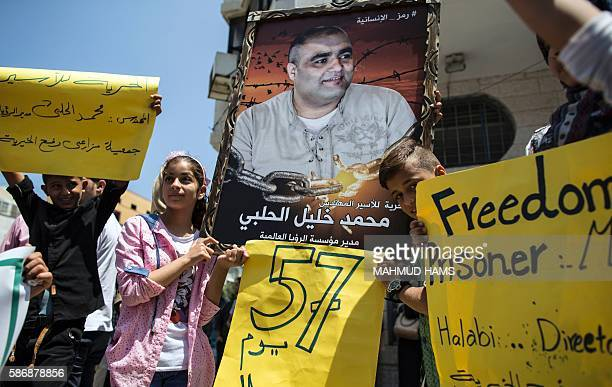 Palestinian children hold posters of Mohammed Halabi the Gaza director of World Vision a major USbased Christian NGO during a protest to support him...