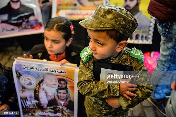 Palestinian children hold their relatives pictures during a demonstration in support of their relatives held in Israeli prisons in front of the...