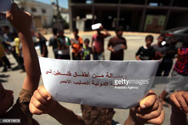 Palestinian children hold up signs reading 'Letter from Palestinian children to International Committee of the Red Cross' during a demonstration in...