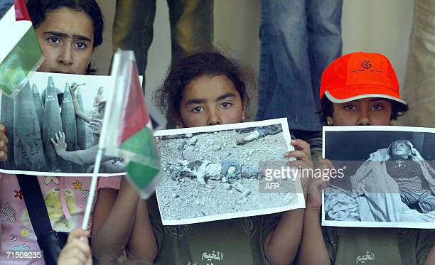 Palestinian children holdup posters of children showing an Israeli child writing on rockets being fired into Lebanon by the Israeli army and dead...