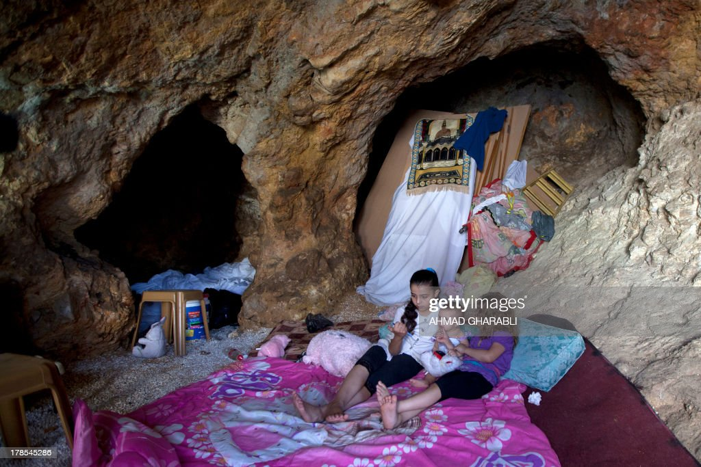 DAVISON - Palestinian children lie on a makeshift bed in the cave that hosts their family since the demolition of their house by Israeli forces on August 29, 2013 in the east Jerusalem neighborhood of Silwan. Israeli forces have destroyed the homes of 716 Palestinians in 2013, according to HRW, which has recorded a three-fold increase in the number of demolitions in east Jerusalem since last year. AFP PHOTO/AHMAD GHARABLI