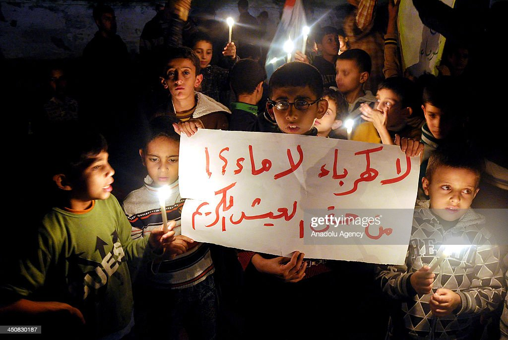 Palestinian children light candles to mark 'Universal Children's Day' in Gaza City calling for peace and end the blockade on Gaza Strip on November 20, 2013.