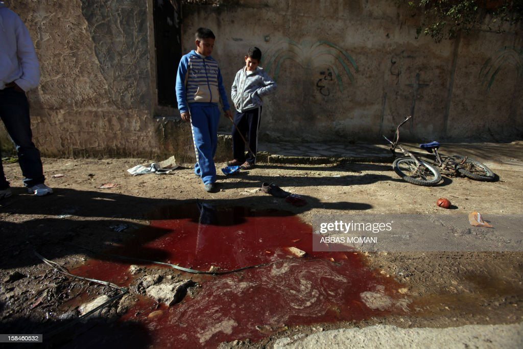 Palestinian children look at blood stains on the ground following a shooting attack in the northern West Bank town of Beit Rima, near Ramallah, on December 17, 2012. Israeli troops arrested four Palestinians on suspicion of shooting offences witnesses told AFP, saying they were accused of shooting at soldiers. AFP PHOTO / ABBAS MOMANI