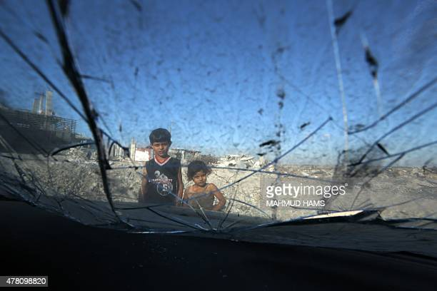 Palestinian children look at the remains of a car on June 22 2015 in Gaza City that was destroyed during 50day war between Israel and Hamasmilitants...