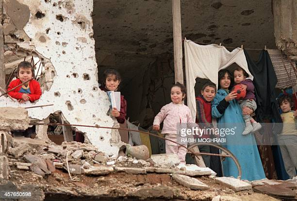 Palestinian children look out from their destroyed home in Shatila refugee camp near Beirut 21 January 1988 as the Syrian forces deploy their...