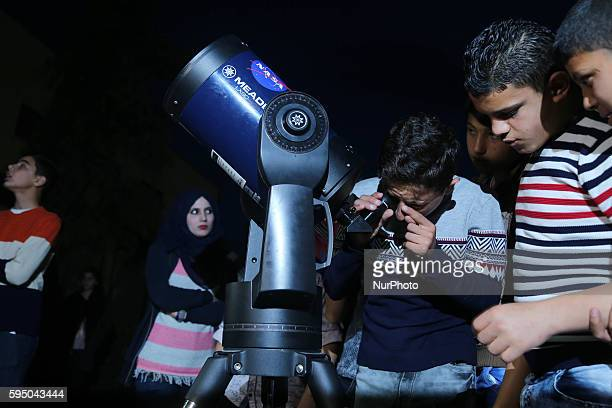 Palestinian children look through a telescope to watch the moon and stars at Alqattan center in Gaza city on March 23 2016