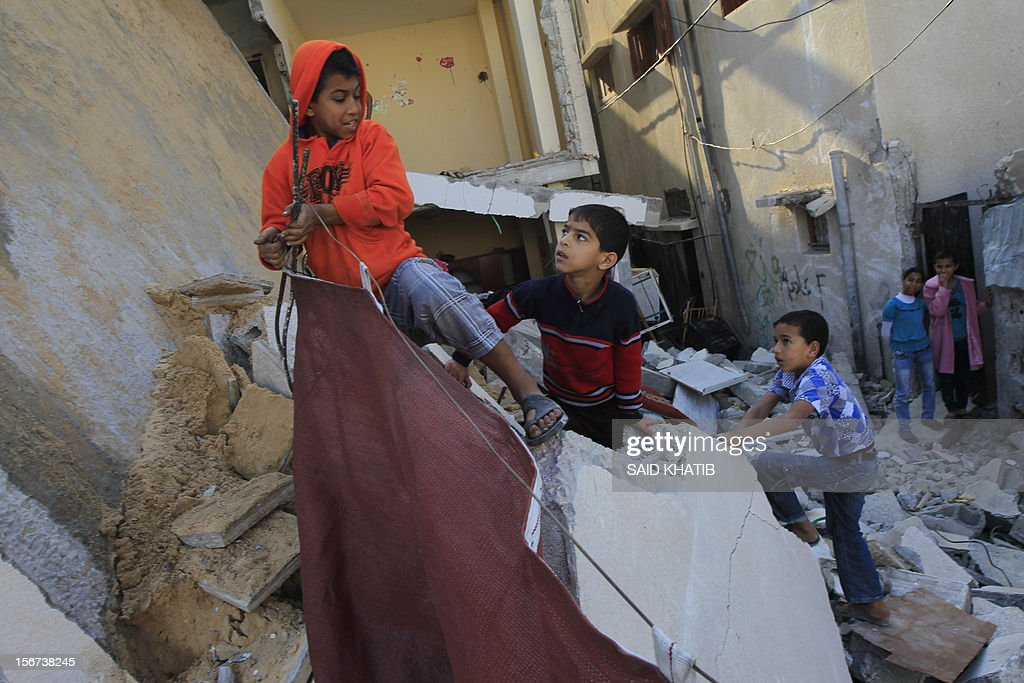 Palestinian children pick up salvageable items from the rubble of a destroyed house following overnight Israeli air strikes in the southern Gaza Strip town of Rafah on November 20, 2012. The Israeli military said it attacked about 100 targets in the coastal strip during the night, using aircraft, warships and artillery.