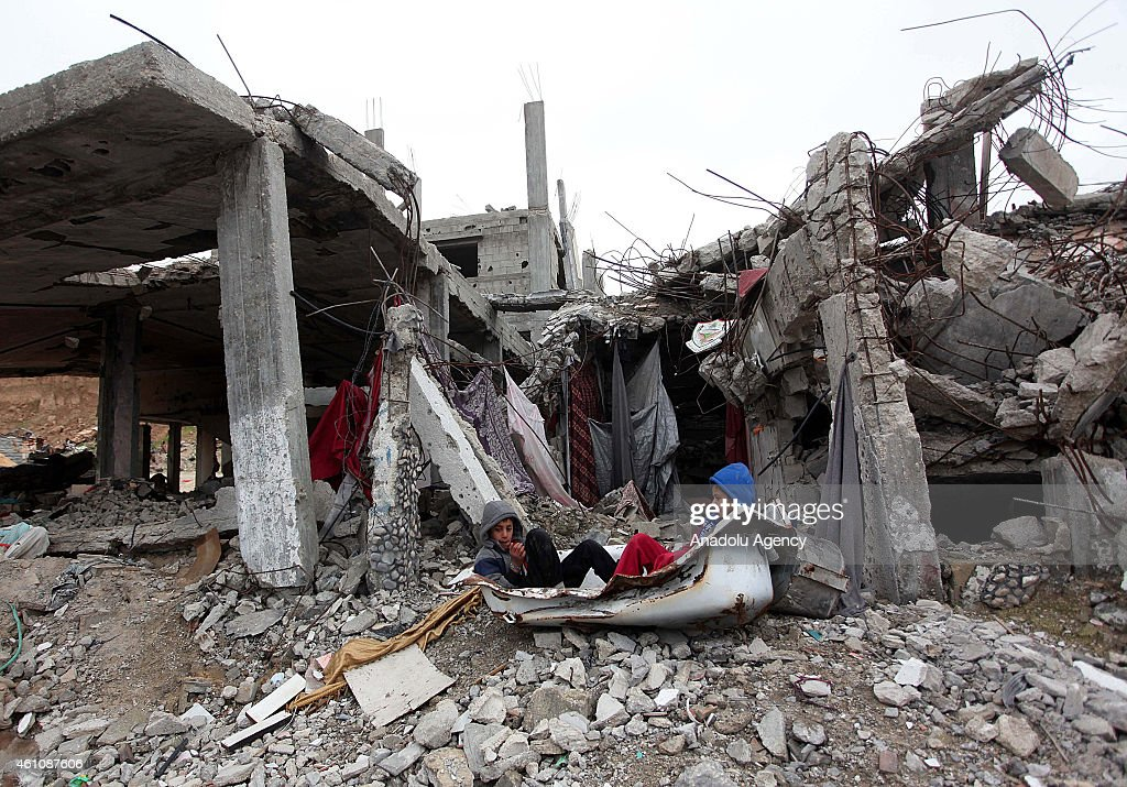Palestinian children play among the debris of houses, destroyed during Israel's latest 50-day airstrikes, in Shujaiyya neighborhood of Gaza City, Gaza on January 06, 2015. Harsh weather conditions of winter worsen the living conditions of Palestinians whose houses were destroyed by Israeli airstrikes.