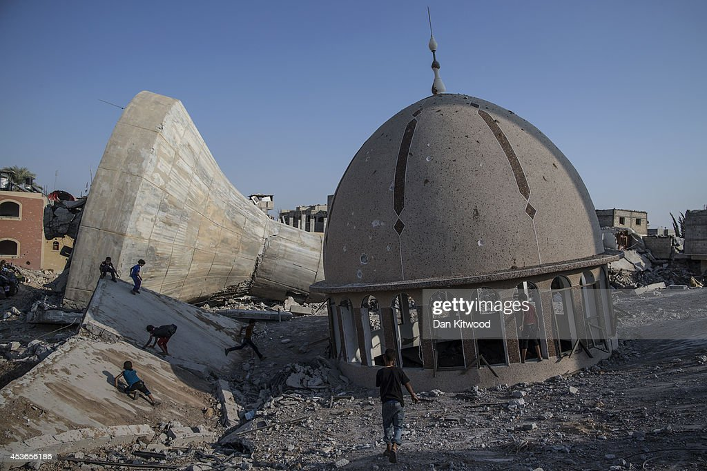 Palestinian children play amongst the ruins of a demolished mosque and water tower on August 15, 2014 in Khuza'a, Gaza. A new five-day ceasefire between Palestinian factions and Israel went into effect yesterday as part of efforts aimed at reaching a permanent truce deal. The Palestinian death toll from Israel's weeks-long military onslaught on the Gaza Strip has risen to 1959, according to a Palestinian Health Ministry spokesman.