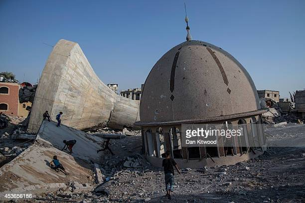 Palestinian children play amongst the ruins of a demolished mosque and water tower on August 15 2014 in Khuza'a Gaza A new fiveday ceasefire between...