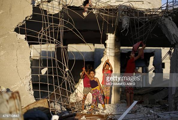 Palestinian children play at the rubble of buildings a year after the 50day war between Israel and Hamas' militants in the summer of 2014 on July 6...