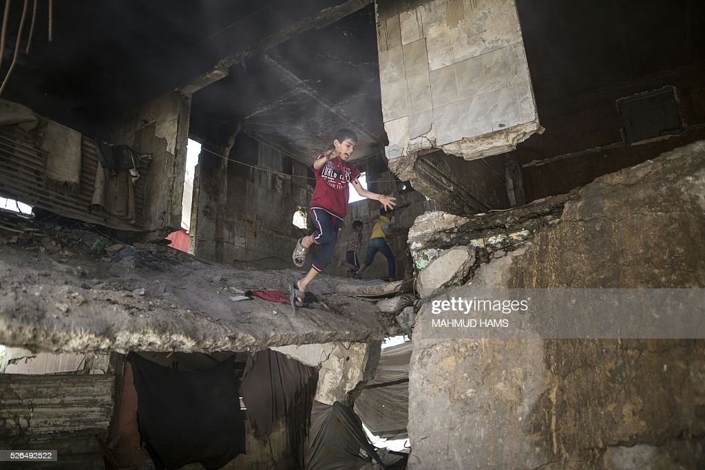 Palestinian children play in a building destroyed during the 50-day war between Israel and Hamas-led militants in the summer of 2014, on April 30, 2016, in Gaza City. Reconstruction aid to over 1,000 families in Gaza has been suspended due to a lack of materials, the United Nations said on April 28, after Israel banned the private import of cement over corruption claims. / AFP / MAHMUD