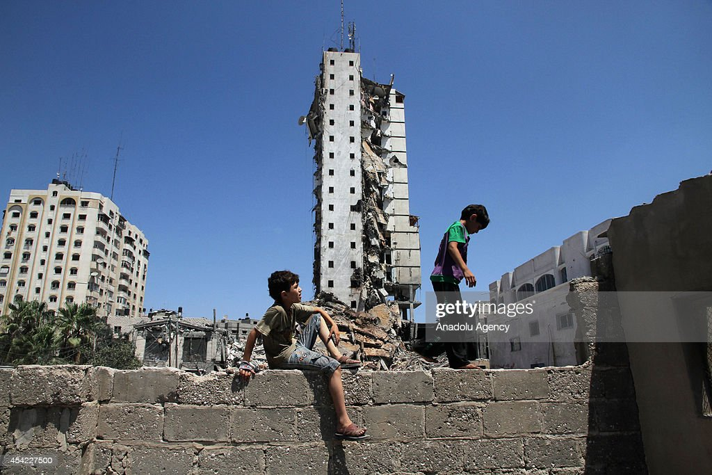 Palestinian children play near the rubble of destroyed Al-Basha Tower, one of the tallest buildings in Gaza City, which was targeted by Israeli air strikes a day before, in western Gaza on August 26, 2014.