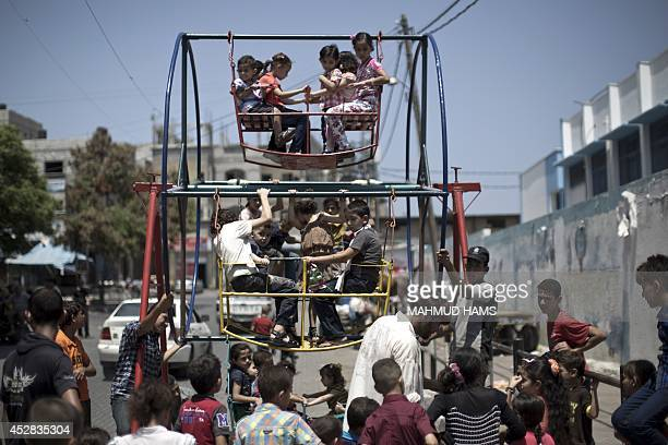 Palestinian children play on a mini ferris wheel outside an United Nations school in Jabalia in the northern Gaza strip on July 28 on the beginning...