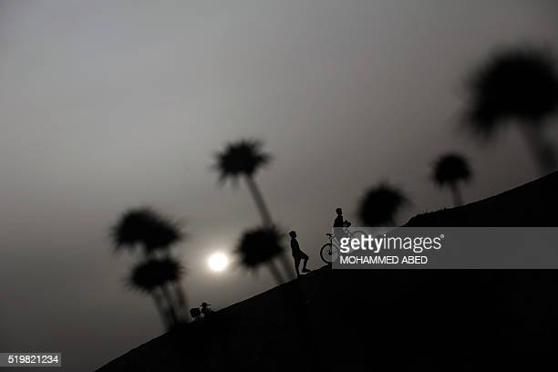 TOPSHOT Palestinian children play on a sandy hill on April 8 2016 in the town of Beit Lahia in the northern Gaza Strip ABED