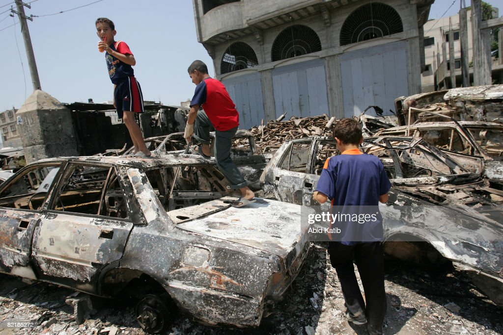 Palestinian children play on burnt out cars one day after clashes between rival forces of Hamas and Fatah movements on August 03 2008 in the Shujaia...