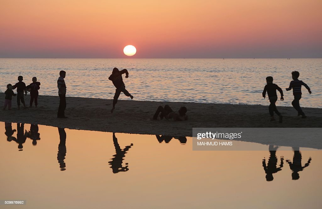 Palestinian children play on the beach in Deir al-Balah in central Gaza on February 13, 2016. / AFP / MAHMUD HAMS