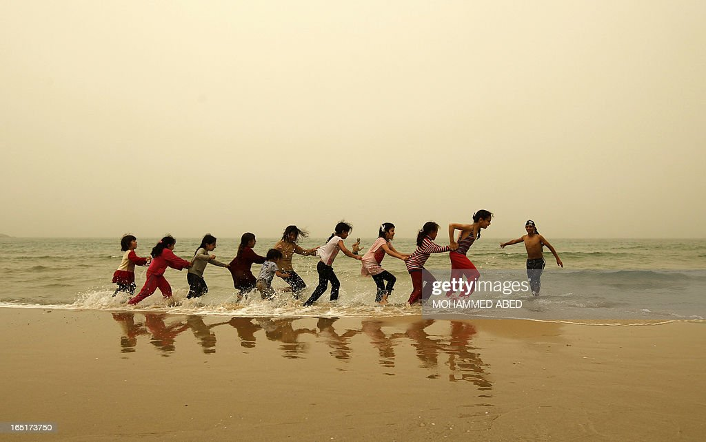 Palestinian children play on the beach in Gaza City during a dust storm on April 1, 2013.