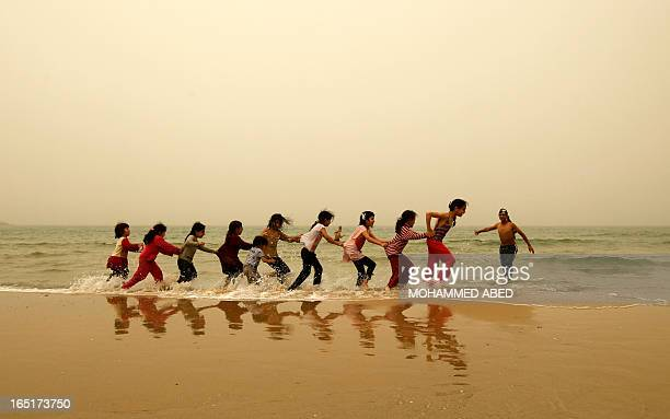 Palestinian children play on the beach in Gaza City during a dust storm on April 1 2013 AFP PHOTO/MOHAMMED ABED