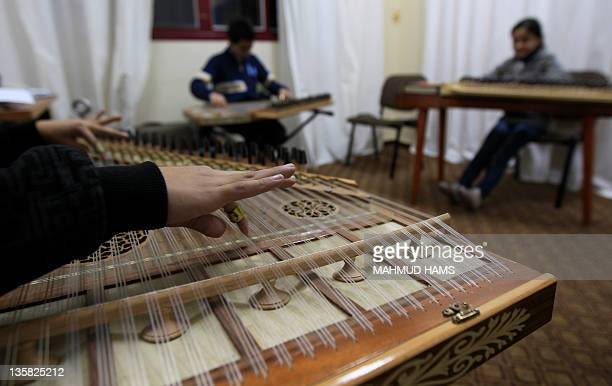 Palestinian children play the qanun a traditional Middle Eastern instrument at the only music school in the Gaza Strip at the headquarters of the...