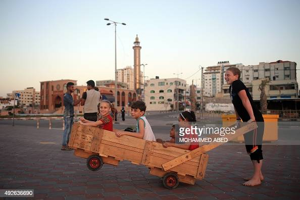 Palestinian children play with a handmade wooden cart in Gaza City on October 14 2015 AFP PHOTO / MOHAMMED ABED